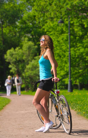 woman with bicycle in park photo