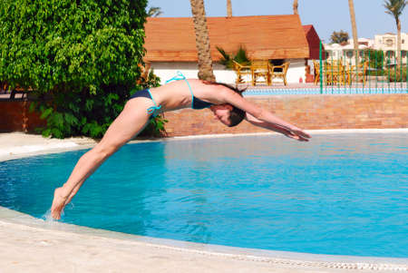 woman jumping into the pool  photo