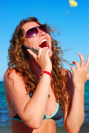 cheerful woman is talking phone near sea photo