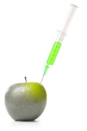syringe in green apple isolated on white photo