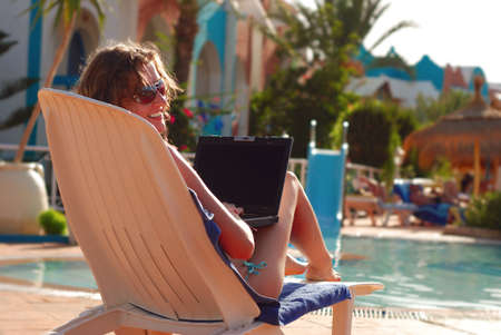 woman in tropical hotel with laptop photo