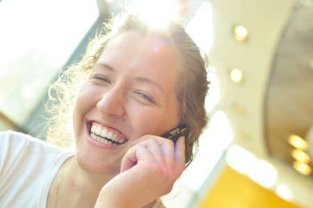 beautiful cheerful woman is talking phone in sunny cafe photo