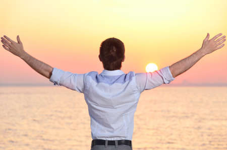 man back view: businessman at sea sunrise Stock Photo