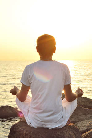man behind: young man is sitting on a stone and looking at sea sunrise. view from behind