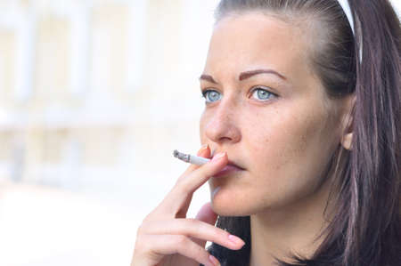 joven fumando: portarretrato de una mujer bonita fumar en la calle
