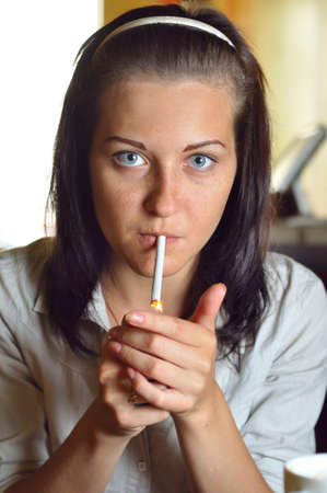 young woman is lighting a cigarette in a cafe photo