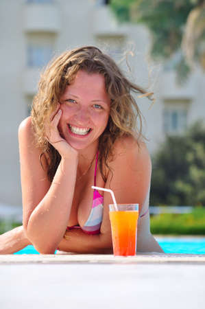 smiling woman in pool with cocktail photo