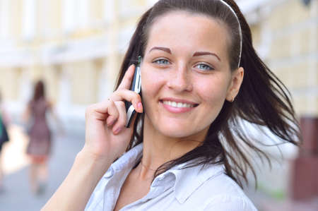 beautiful smiling woman is talking phone at sunny street photo