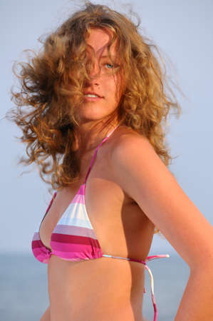 beautiful young woman with flying hair near the sea at sunset photo