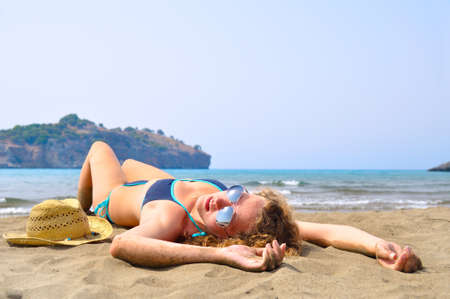 sexy woman is lying on the beach and looking at camera Stock Photo - 8041476