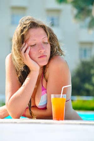 sad pretty bored woman is sleeping in the hotel swimming pool photo