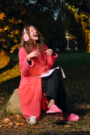 happy woman is laughing on magazine at forest in undress photo