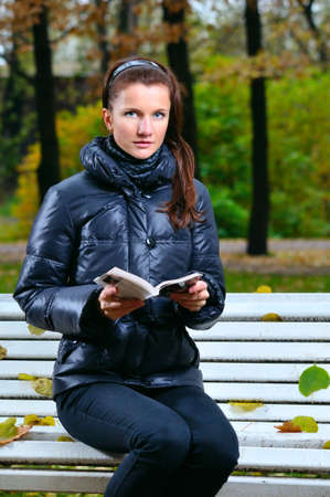 young woman is sitting on a bench in an autumn park and reading photo