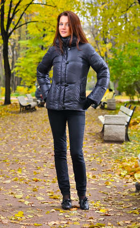 young woman is standing at autumn park photo