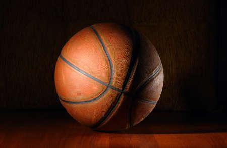 terrain de basket: ballon de basket � la tomb�e de la nuit sur le plancher en bois  Banque d'images