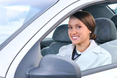 happy business woman in a car is looking at camera photo