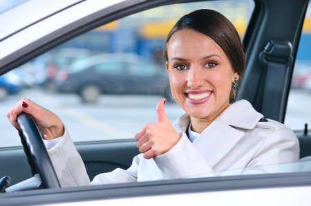 happy woman is showing a thumb from a car photo