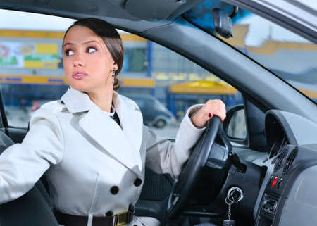 car park interior: woman in a car is looking backwards trying to move back Stock Photo