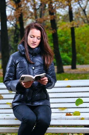 beautiful woman is sitting in park and reading photo