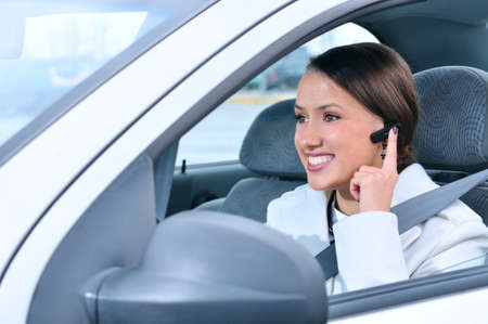 safe driving: beautiful woman is safely talking phone in a car using a bluetooth headset Stock Photo