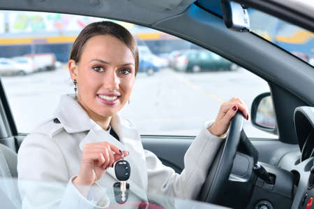 happy woman is showing keys of her new car photo