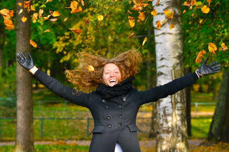 happy woman is throwing dry autumn leaves in park  photo