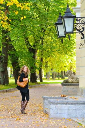 woman is walking at autumn city park photo