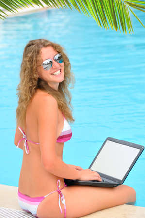 woman is sitting on the edge of swimming pool with laptop photo