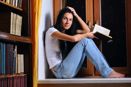 beautiful woman is sitting on a windowsill and holding a book photo