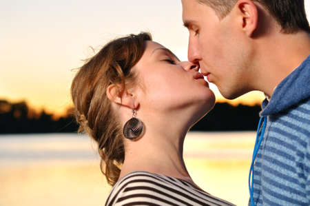 young attractive couple is kissing at sunset photo