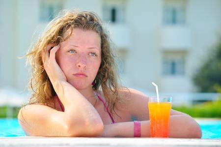 sad pretty bored woman is boring in the hotel swimming pool  photo