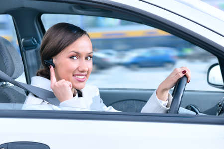 safely: beautiful woman driver is safely talking phone in a car using a bluetooth headset