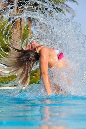 slim woman is spectacularly jumping out of pool and shaking hair photo