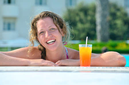 attractive woman is smiling from swimming pool in resort photo