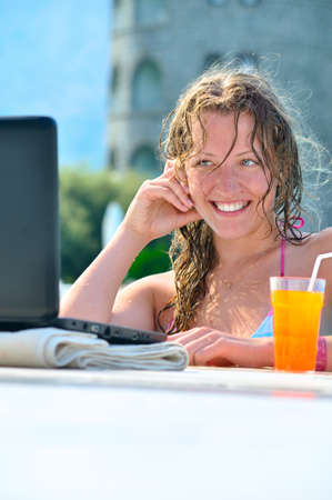 beautiful woman is using laptop in the swimming pool Stock Photo - 8345835