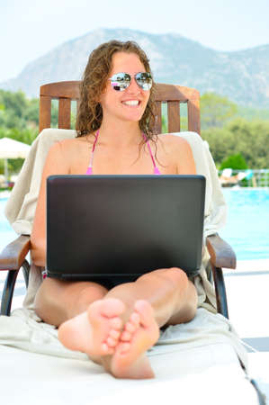 beautiful woman is sitting on wooden chair near the pool with laptop photo