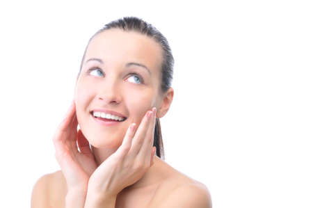 beautiful happy woman is looking sideways and touching her face photo