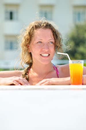 close up of pretty woman looking sideways in swimming pool with cocktail  photo
