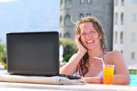 beautiful woman is using laptop at poolside and looking at camera photo