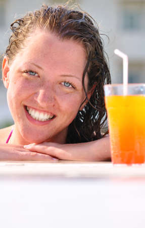 close up of pretty woman in swimming pool with cocktail  photo