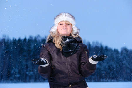 happy young woman is enjoying snowy winter evening photo