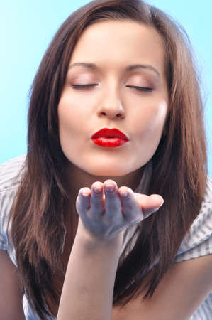 sexy long haired business woman with deep red lips and closed eyes is sending kiss photo