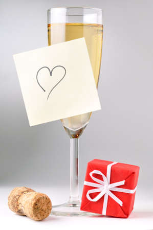 champagne glass with heart on sticky note, red gift box and cork photo