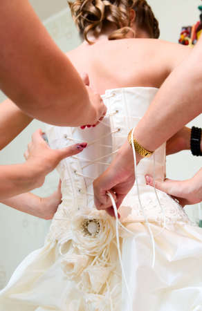 getting a bride: bride friends are helping to dress her before wedding Stock Photo