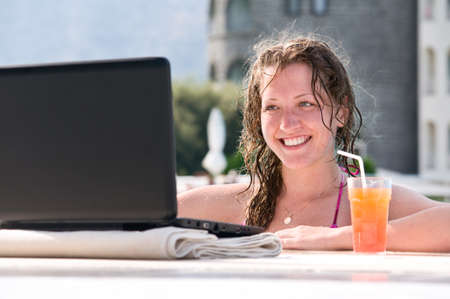 woman is using laptop from swimming pool near the hotel  photo