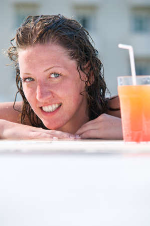 close up of pretty woman with wet hair in swimming pool with cocktail  photo