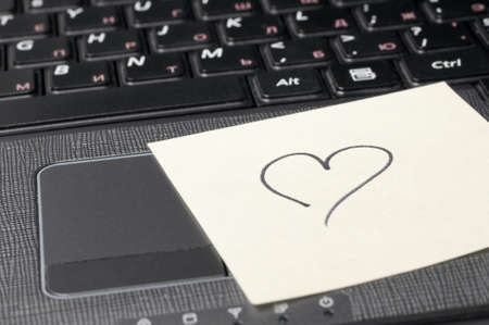 heart on sticky note on computer keyboard  photo