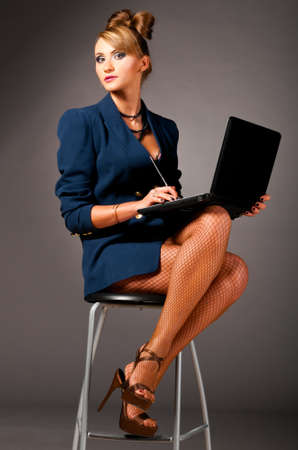 sexy provocative business woman at office with laptop photo
