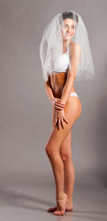 beautiful bride is standing in lingerie and wedding veil and looking sideways photo