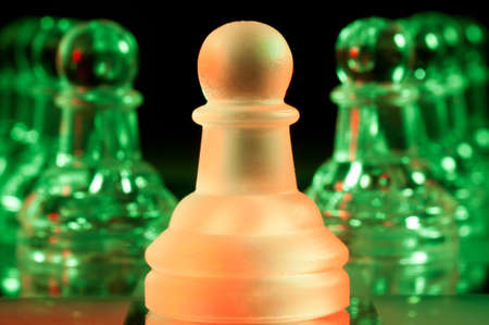red leader and rows of green glass chess pawns is standing on board in dark photo